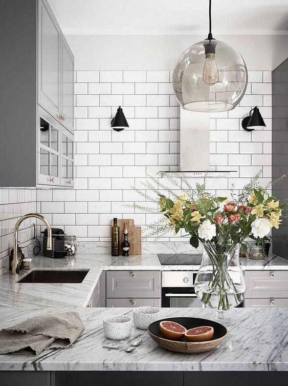 una cucina nordica di ispirazione retrò con piastrelle bianche, ripiani in pietra, armadi grigi e lampade a sospensione