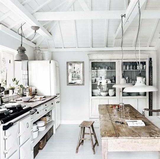 una cucina nordica bianca con un buffet imbiancato, lampade a sospensione, un set da pranzo in legno grezzo