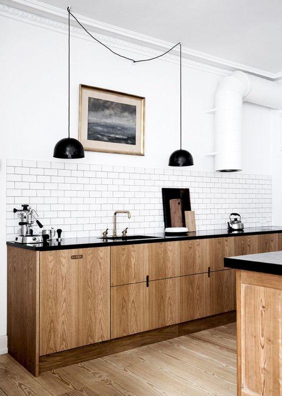 una cucina scandinava di ispirazione retrò con armadi in legno chiaro, controsoffitti neri, lampade a sospensione nere, un backsplash di piastrelle bianche
