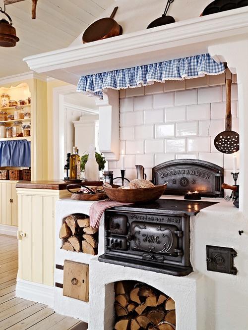 una cucina nordica retrò con stufa, legna da ardere, piastrelle bianche della metropolitana, armadietti di latticello e tocchi di blu