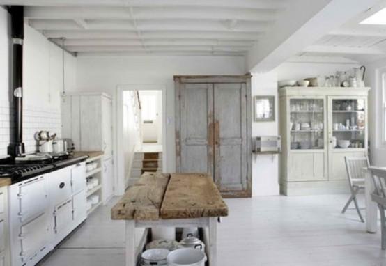 una cucina scandinava vintage e shabby chic con pensili bianchi, una stufa retrò, un buffet azzurro shabby chic, un buffet in vetro, un'isola cucina con piano in legno grezzo