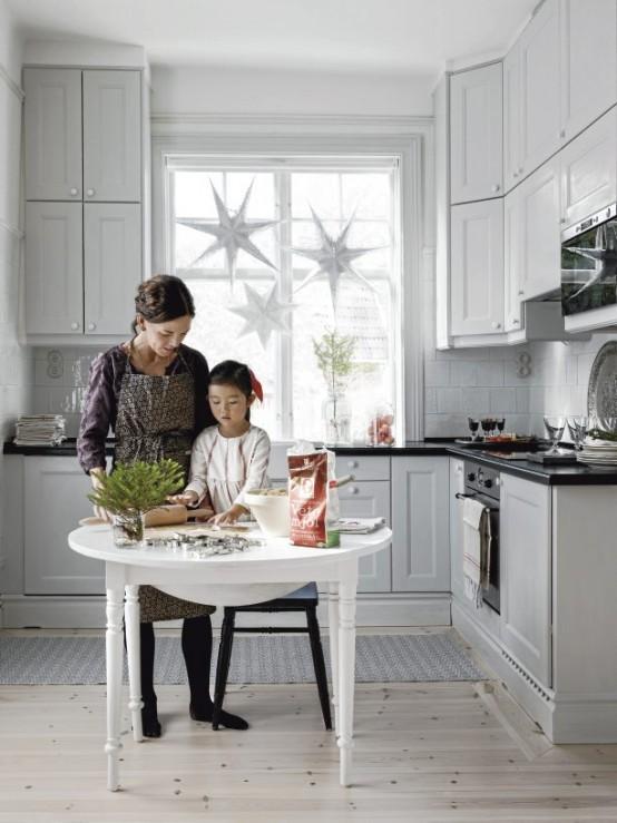 una cucina nordica neutra con mobili vintage, stelle appese alla finestra, un tavolo rotondo