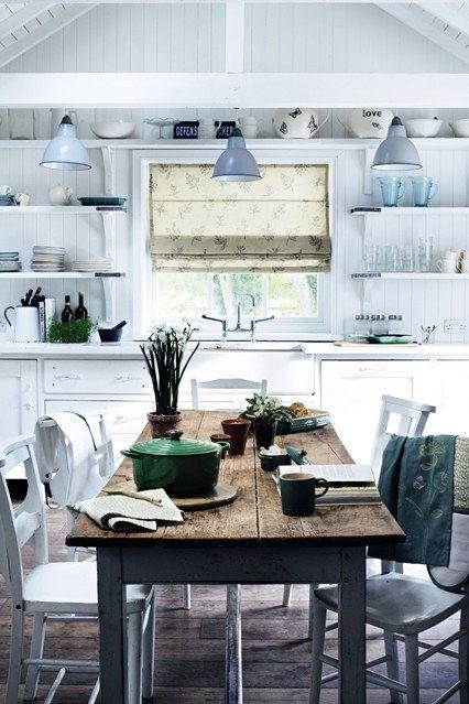 una cucina nordica bianca con pareti in legno, scaffali aperti, armadi vintage, un tavolo rustico e sedie imbiancateed