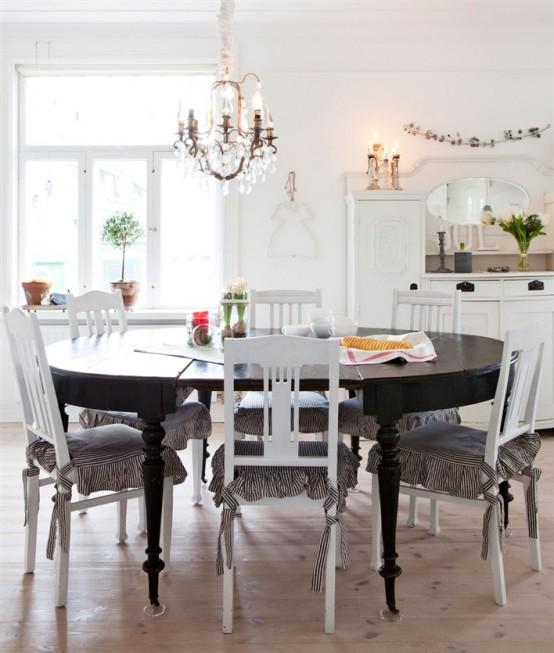 una cucina scandinava vintage con armadi bianchi, un lampadario di cristallo, un tavolo rotondo nero e sedie vintage bianche