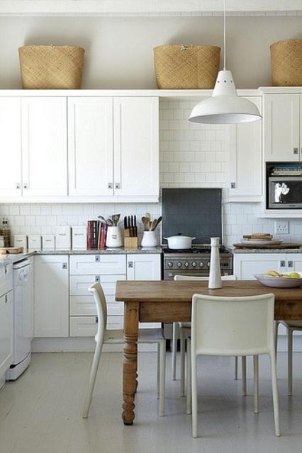 un'elegante cucina scandinava neutra con armadi vintage, un paraschizzi in piastrelle bianche, un tavolo in legno rustico e lampade a sospensione