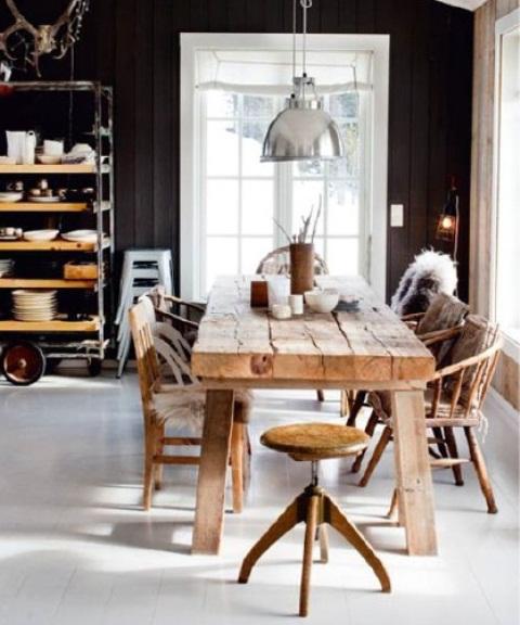 una cucina nordica in bianco e nero, un set da pranzo rustico in legno grezzo, una lampada a sospensione in metallo e uno sgabello