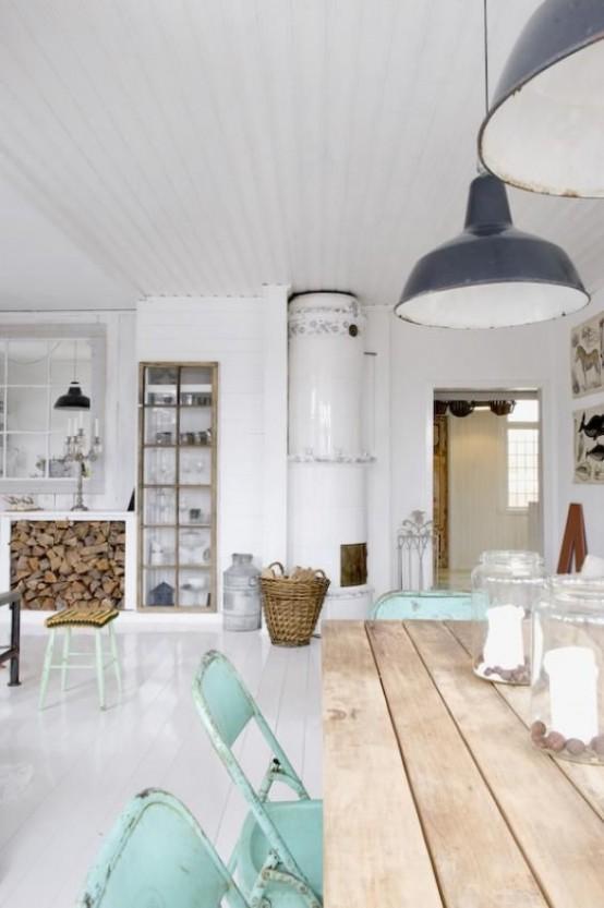 una cucina nordica con tavolo in legno, sedie color menta, lampade a sospensione vintage, fornelli e buffet integrato