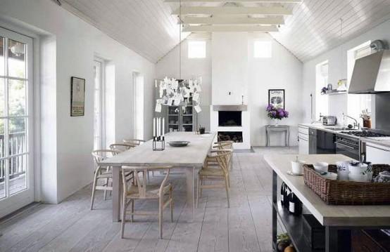 una cucina nordica neutra con armadi in metallo, un set da pranzo imbiancato e lampade a sospensione