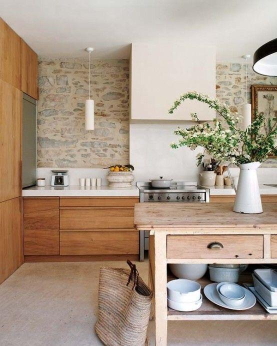 un'accogliente cucina dai toni della terra con un muro in pietra, mobili dalle tinte calde, un'isola cucina in legno e lampade a sospensione