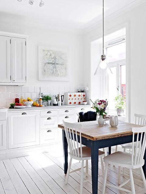 una cucina scandinava bianco puro con armadi retrò, una lampada a sospensione in vetro e un tavolo da pranzo vintage navy