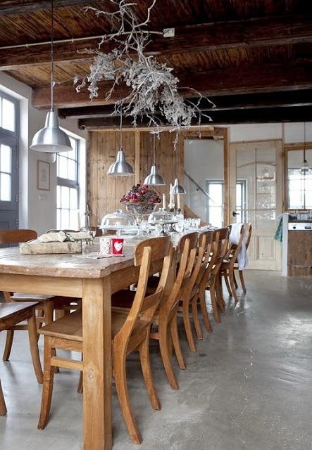 una cucina scandinava rustica con un set da pranzo in legno, rami imbiancati e lampade a sospensione argentate oltre a un pavimento in cemento