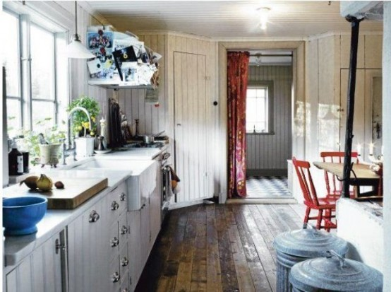 una cucina rustica scandinava con armadietti bianchi e pareti imbiancate, sedie rosse e tocchi di blu qua e là
