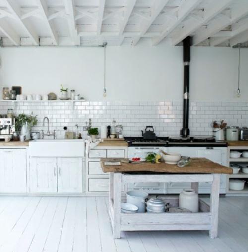una cucina nordica bianca con armadi bianchi, un'isola da cucina imbiancata, una stufa vintage e tutte le superfici bianche