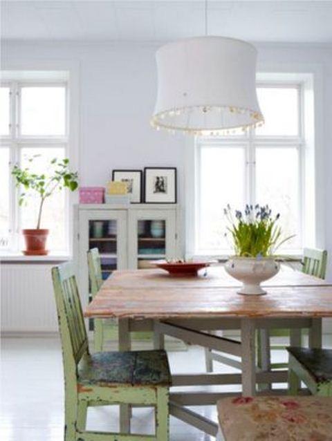 uno spazio shabby chic con un tavolo rustico, sedie shabby verdi e uno sfondo bianco puro