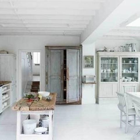 una cucina nordica bianca con un buffet bianco sporco, un set da pranzo bianco, un armadio shabby chic e un'isola cucina rustica