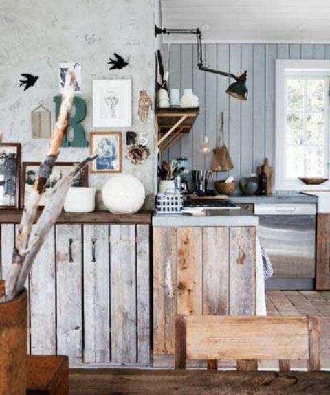 un'accogliente cucina rustica con pareti azzurre, armadi in legno grezzo, rami e lampade da parete