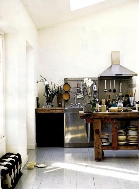 una cucina scandinava vintage con pavimento imbiancato e pareti bianche, un'isola da cucina in legno grezzo, tocchi di metallo e legno grezzo