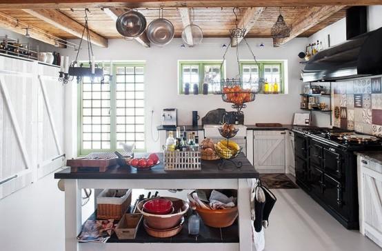 un'accogliente cucina scandinava bianca con una grande cucina e cappa nera, con un'isola cucina in bianco e nero e un soffitto in legno con travi e pentole