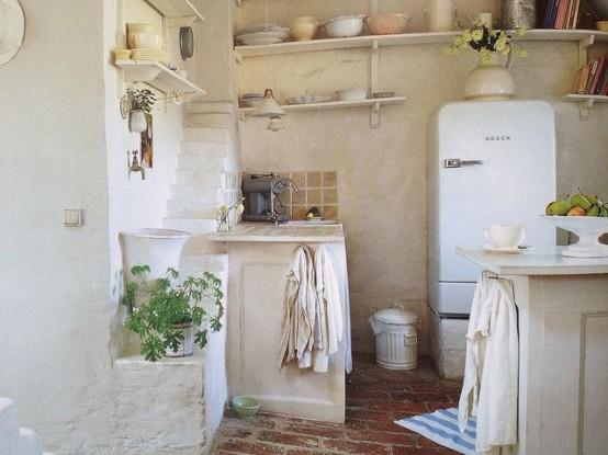una cucina in pietra bianca con pareti in gesso, con ripiani aperti, un'isola cucina e un frigorifero moderno