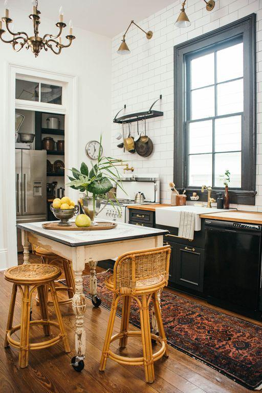 una cucina chic che abbina armadi neri con ripiani neutri, un tavolo shabby chic, sedie vintage in rattan e lampade industriali
