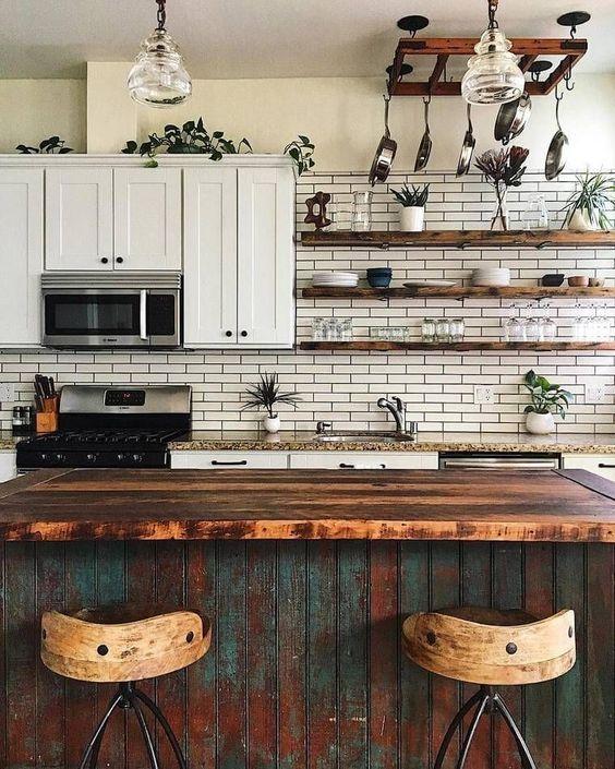 un vintage chic incontra una cucina boho con un'isola cucina shabby chic, piastrelle bianche, piante in vaso e lampade a sospensione