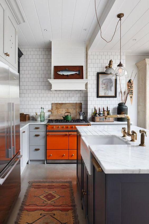 una luminosa cucina eclettica con fornello arancione, armadi blu navy e grigi, ripiani in pietra bianca e opere d'arte accattivanti