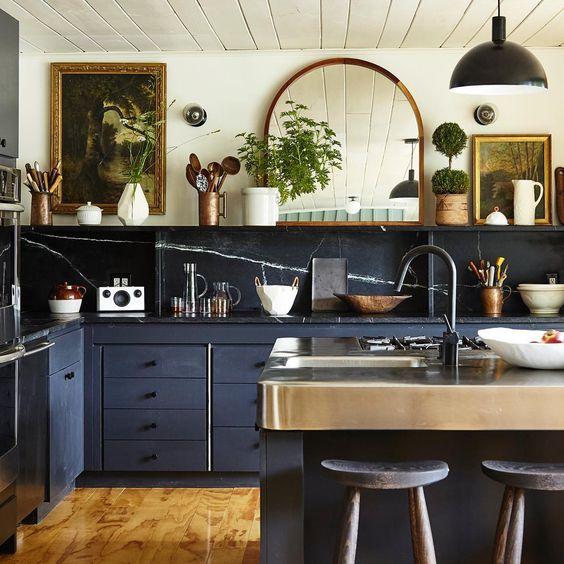 una splendida cucina eclettica che combina alzatina e controsoffitti in pietra, armadi blu scuro e opere d'arte vintage e uno specchio