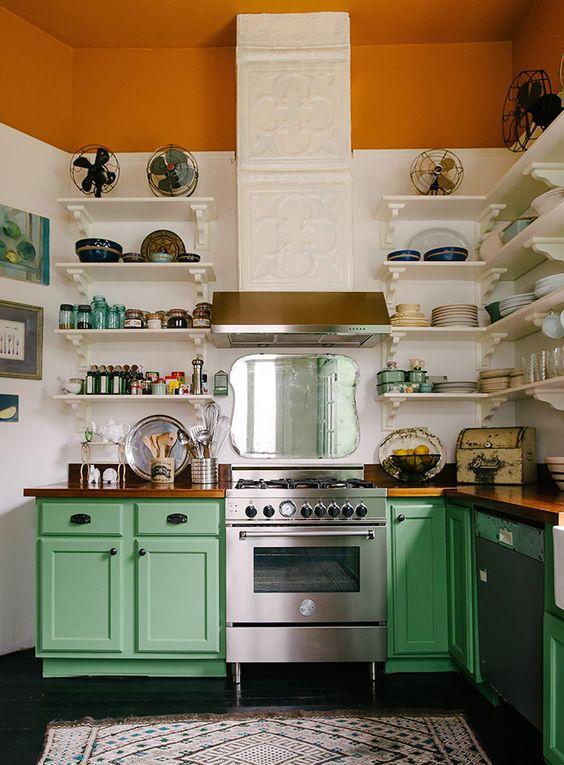 un vintage colorato incontra una cucina rustica con un cappuccio piastrellato, una striscia ruggine, armadi verdi e mensole bianche