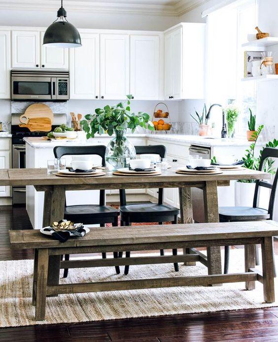 una fresca cucina contemporanea in bianco con una zona pranzo rustica con panche e tocchi di blakc per il dramma