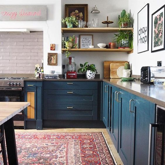 un contemporaneo incontra la cucina boho con un tappeto boho, armadi blu scuro, un piano di lavoro in pietra e piante in vaso