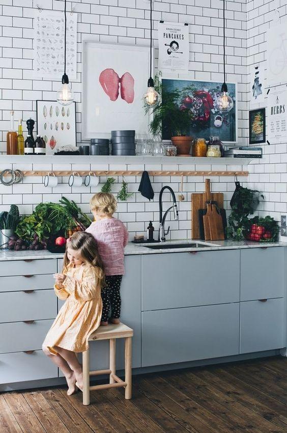 un accogliente contemporaneo incontra la cucina industriale con piastrelle bianche della metropolitana, armadi azzurri, molte opere d'arte e lampadine a sospensione
