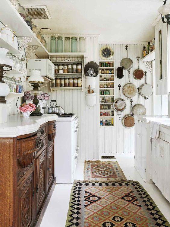 un raffinato buffet in legno tinto scuro abbinato a mobili shabby chic bianchi, un tappeto boho e pareti a battente