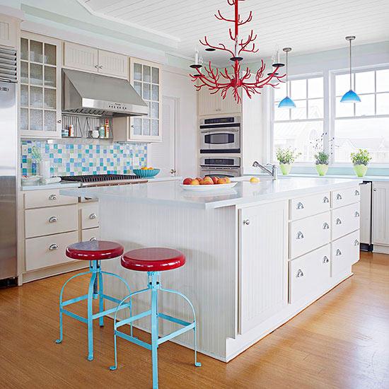 una cucina da cottage bianca decorata con un alzatina in piastrelle di vetro, due sgabelli e un lampadario rosso unico