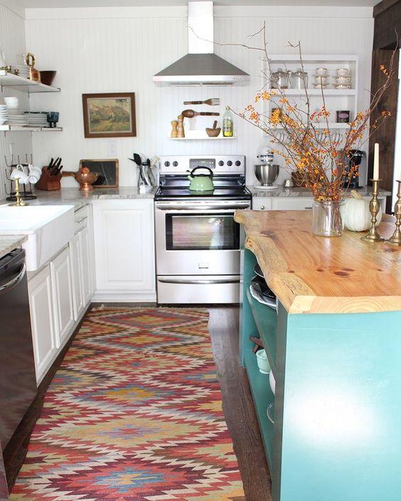 una cucina tradizionale bianca, un tappeto boho colorato, un'isola da cucina blu con un piano di lavoro in legno con un bordo vivo
