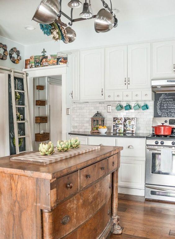 una cucina tradizionale bianca con ripiani scuri arricchita con un'isola da cucina in legno vintage per renderla più rilassata