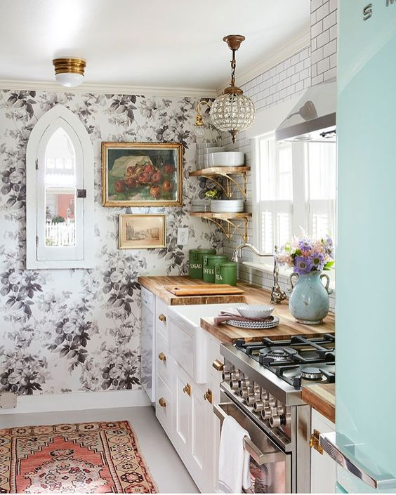 i tradizionali armadi bianchi con ripiani in macelleria sono combinati con un muro floreale, una lampada glam e un tappeto boho