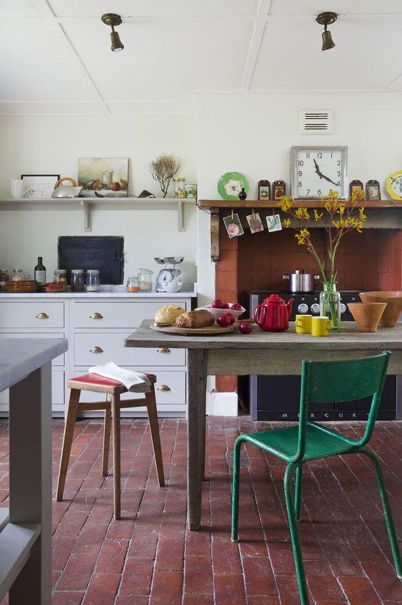 eleganti armadi bianchi, un tavolo in legno rustico, sgabelli e sedie vintage in vari colori e un camino rivestito di piastrelle