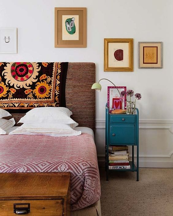 una luminosa camera da letto eclettica con un letto imbottito, una cassapanca in legno, un comodino vintage e arte astratta