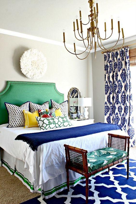 una colorata camera da letto eclettica in un audace blu e verde smeraldo, con un mix di stampe e tocchi vintage
