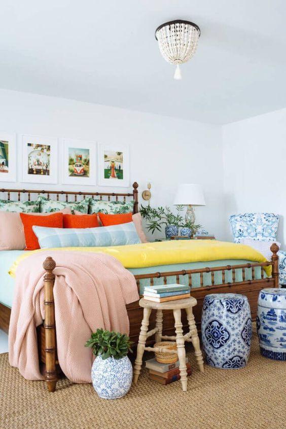 un colorato spazio per dormire eclettico con un letto di bambù, una galleria a parete con foto delle vacanze, eleganti tavolini blu e bianchi e un lampadario a perline