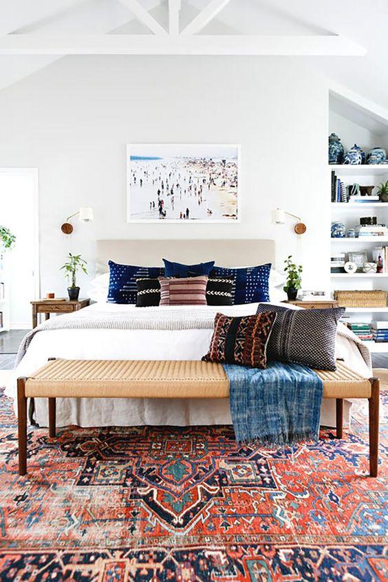 una camera da letto eclettica piena di luce con un letto imbottito, una panca intrecciata, mensole incorporate, comodini in legno e vegetazione in vaso