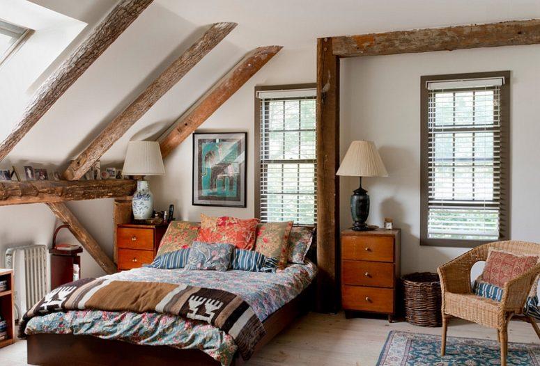 una confortevole camera da letto eclettica con mobili moderni della metà del secolo, travi in legno, sedie in vimini ed eleganti lampade vintage