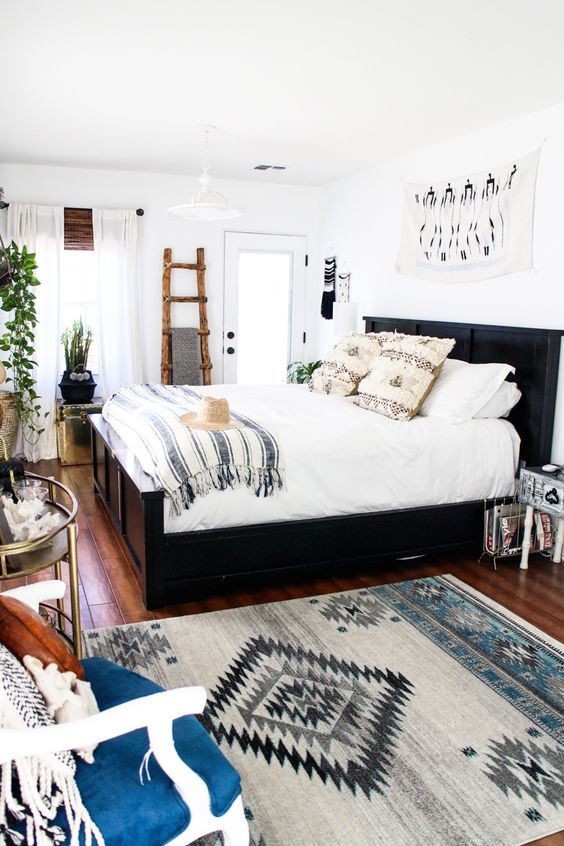 una camera da letto eclettica piena di luce con un letto scuro, una scala rustica per riporre oggetti, stampe, tavoli glam e vegetazione in vaso