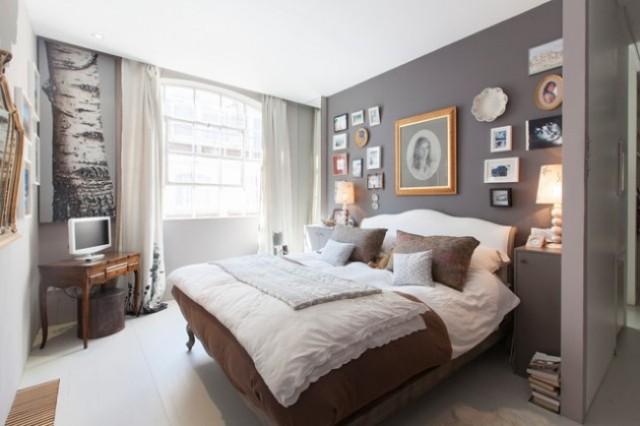 una camera da letto eclettica monocromatica in grigio, bianco e marrone intenso, con una galleria a muro di ispirazione vintage, un letto e un tavolo raffinati e comodini moderni