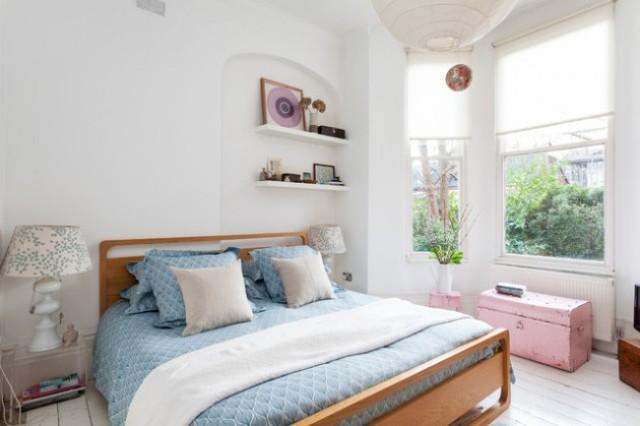 una camera da letto eclettica con un moderno letto in legno, una cassettiera e uno sgabello rosa, lampade di ispirazione vintage e moderni scaffali incorporati