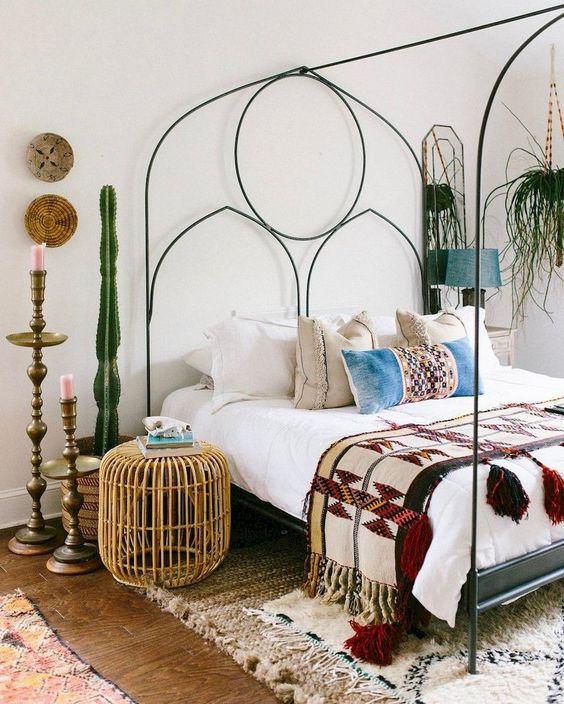 una camera da letto eclettica con un letto in metallo con decorazioni, cactus in vaso e vegetazione, un ottomano in rattan e portacandele vintage