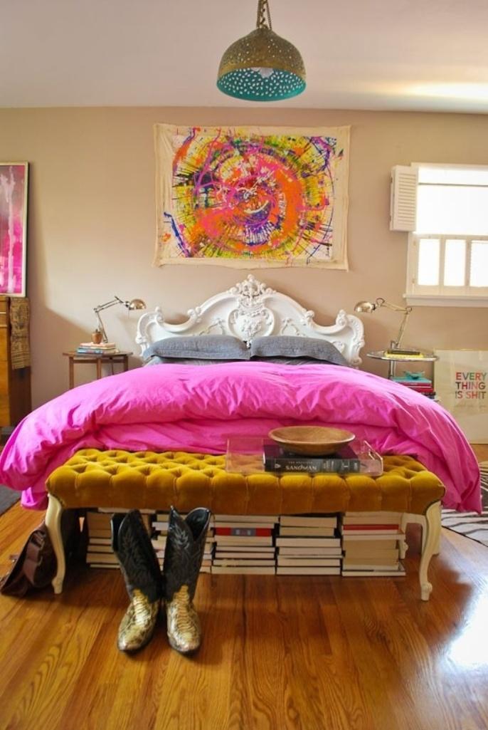 una camera da letto eclettica super luminosa con opere d'arte audaci, un ottomano trapuntato senape, pile di libri, un letto raffinato e comodini non corrispondenti