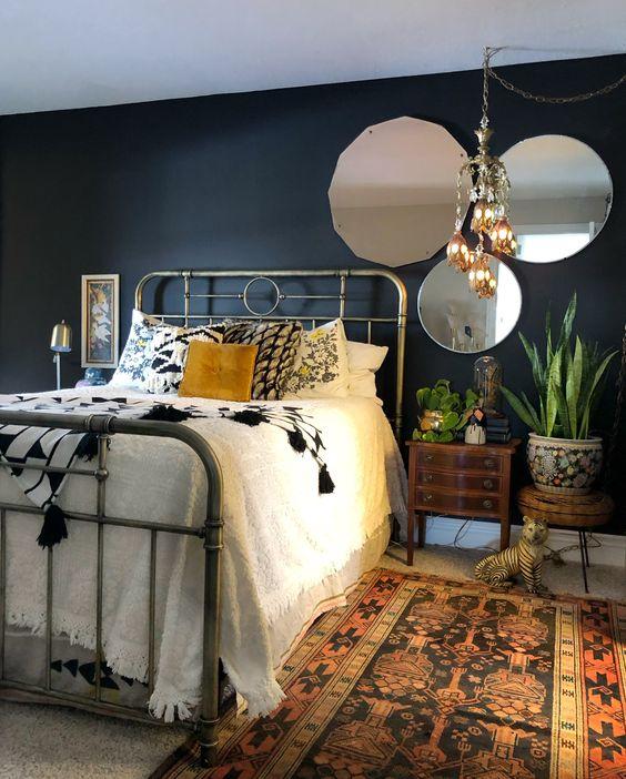 una camera da letto eclettica lunatica con tappeti boho e un lampadario, specchi vintage e un letto in metallo e comodini moderni della metà del secolo