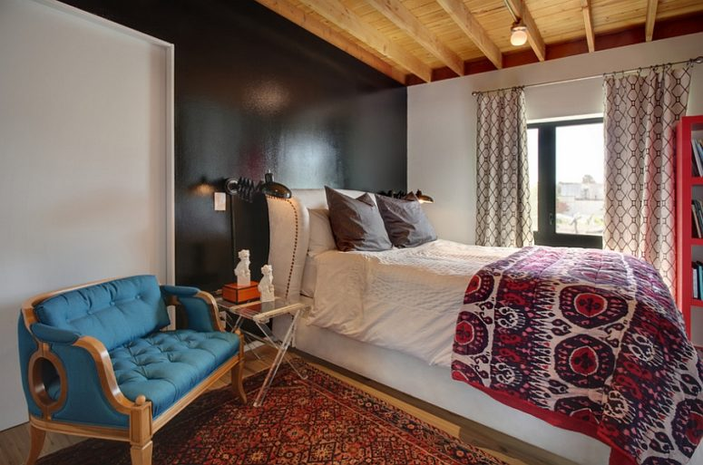 una camera da letto eclettica caratterizzata da una bella transizione tra vari stili di arredamento e un mix di colori e stampe