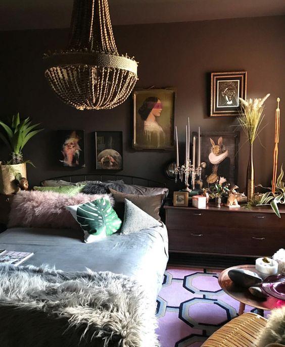 uno spazio eclettico lunatico con pareti scure, una galleria a muro di ispirazione vintage, biancheria da letto e accessori audaci